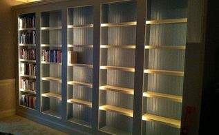 a new library, home decor, shelving ideas, The shelves are done It We painted them the same color as the house trim BEHR sensible hue Here we re loading the library shelves The in built lighting really shines here