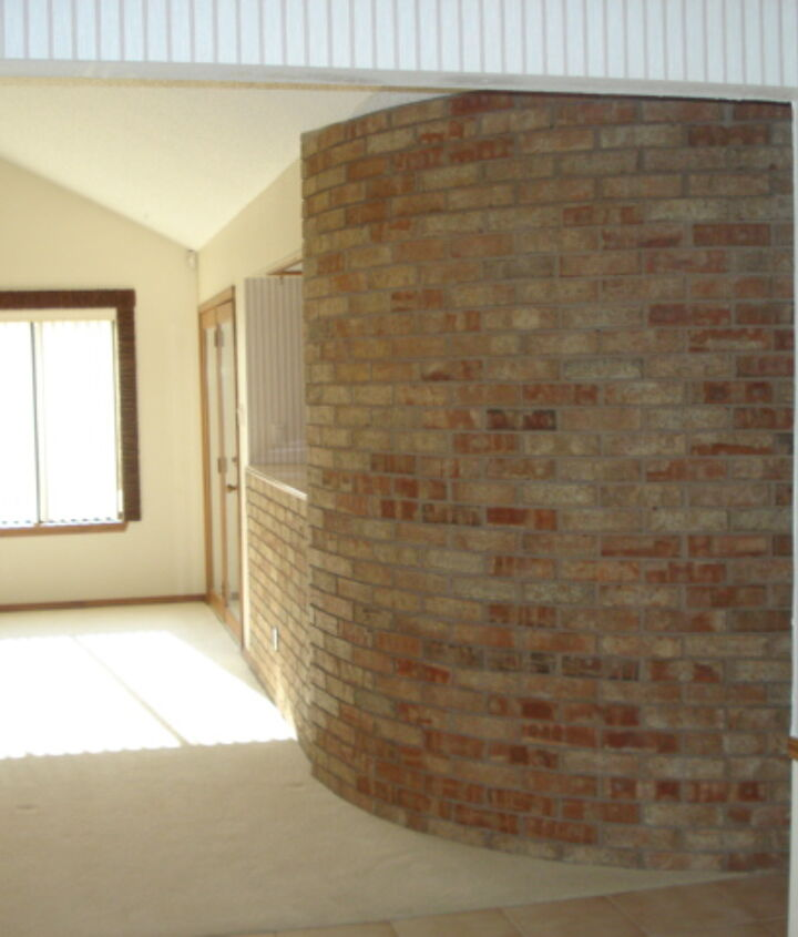 Right side of living room shows same window, curved  brick wall and planter.