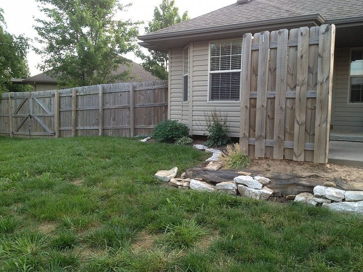 Now facing the house with left side of patio and small fence.