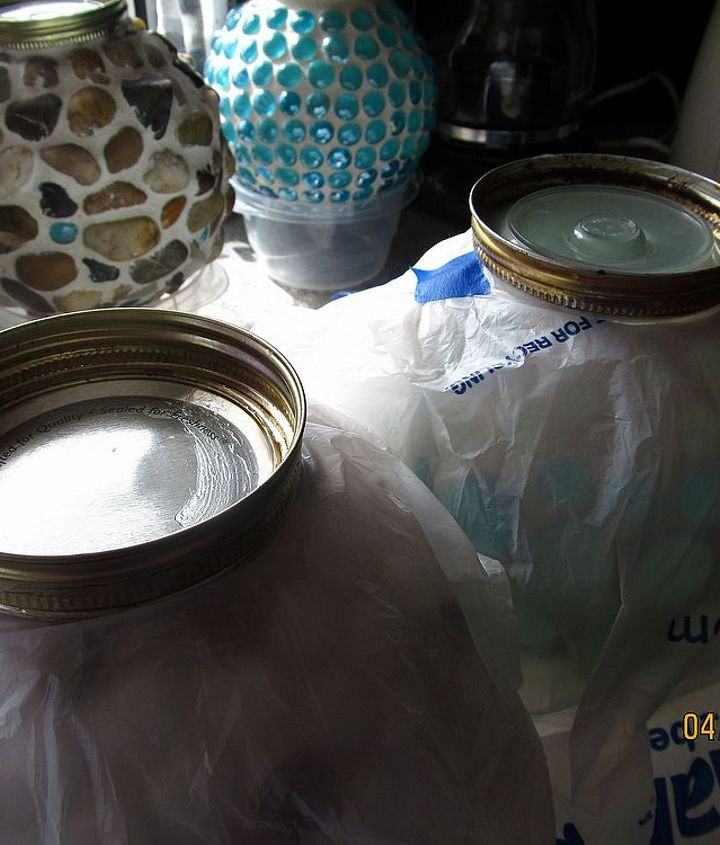 garden globes, crafts, mason jars, After letting the bases dry over night resting on plastic bowls in the background time for a paint job To protect the globes I cut circles in the bottom of grocery bags and taped them tight around the globes