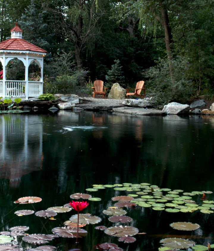 A large pond has a gazebo and firepit nearby.