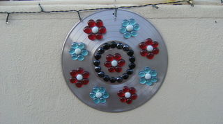 vinyl record clock, crafts, repurposing upcycling, I spray painted the record then drilled a hole in the top to hang it Simply added gems using silicone