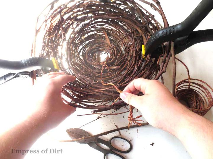 Start winding the grape vine in circles, starting with the bottom center of the nest. Clamps hold things in place until wires are added. http://www.empressofdirt.net/gardenartbirdnest/