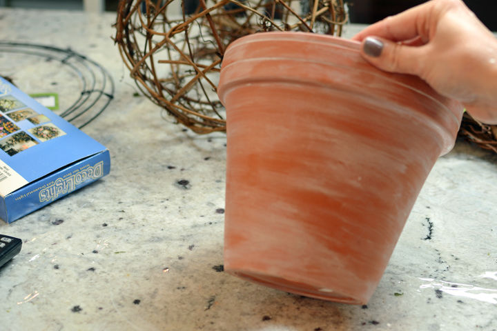 I started with a terra cotta pot...because I love terra cotta. Using some watered down paint, and an easy little painting technique, I gave the pot an aged patina.