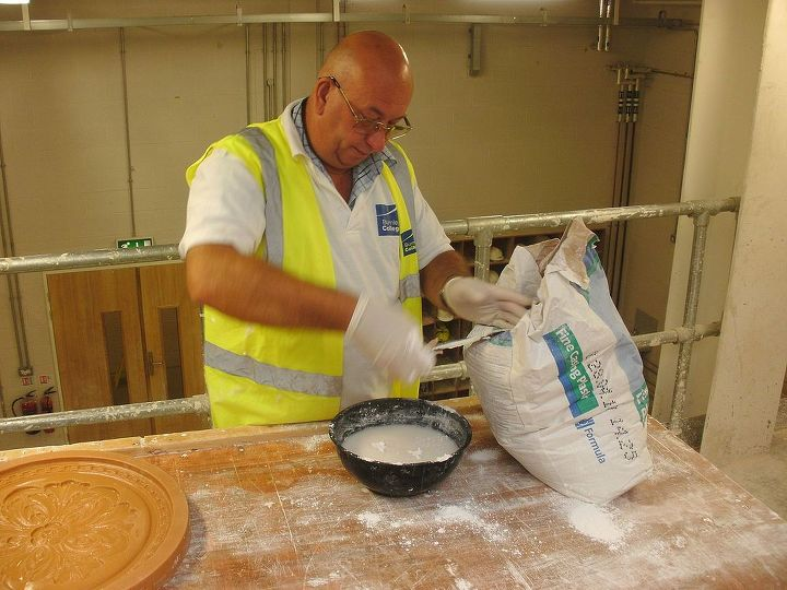 Using a gloved hand , the casting plaster is mixed in a bowl of clean cold water