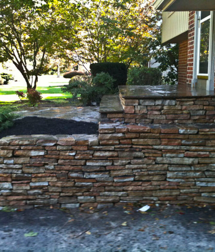 The original brick wall was torn out and in it's place we constructed a natural stacked stone wall to border the driveway.