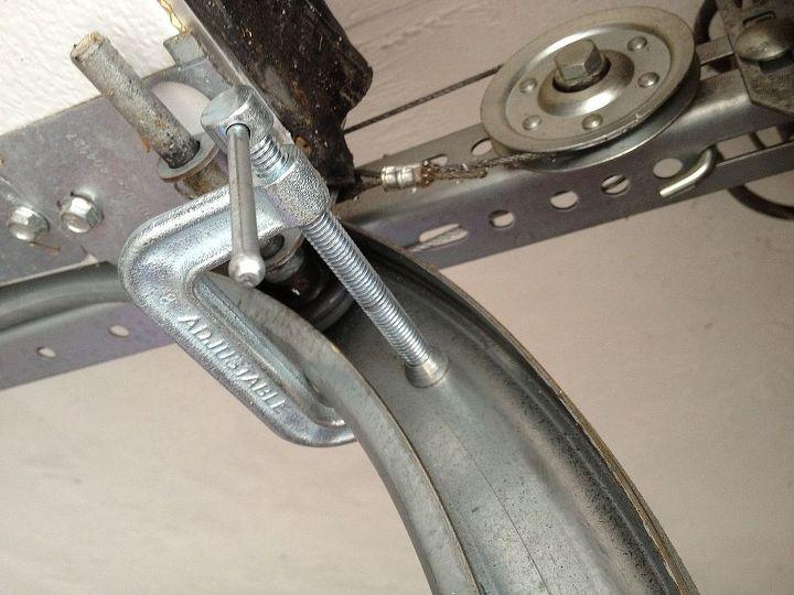 Place C-Clamps on garage door track below last roller