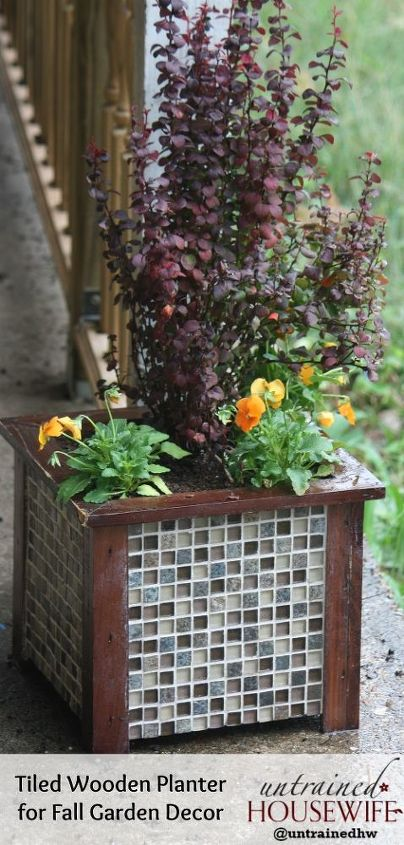 This simple wooden container was transformed into upscale garden and porch decor with $20 worth of tiles. Stunning transformation. It's planted with a Japanese barberry and bright orange violas for a fiery fall color scheme.