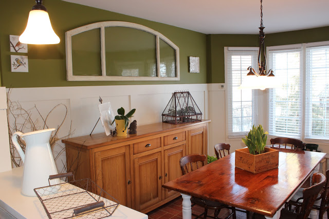 Kitchen Eating Area with board and batten panelling, reclaimed wood table and old transom window repurposed.