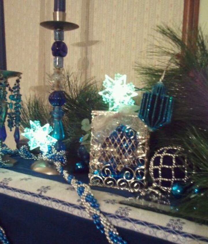 Beaded garland, tinsel dreidels, colored glass balls in the tzedakah (charity) box, 6 sided lighted snowflakes (like the Jewish star, available at Big Lots), and a repurposed ornament with winter greens as a backdrop.