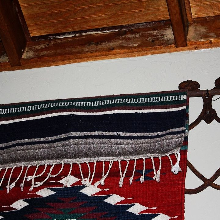Hanging rugs on the wall is nothing new, but I still love the look.  I used an old frog gig and ancient iron candelabras turned upside down to hold my rugs.