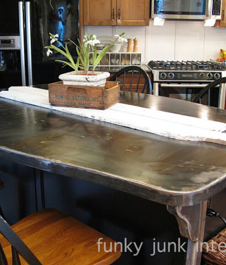 This double sided metal kitchen island top serves double duty. It's a counter and kitchen table all in one. The curvy corners help to visually diminish the size as well as add a personal touch.